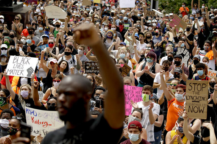 People hold signs as they listen to a speaker in front of city hall in downtown Kansas City, Mo., Friday, June 5, 2020, during a rally to protest the death of George Floyd who died after being restrained by Minneapolis police officers on May 25. (AP Photo/Charlie Riedel)