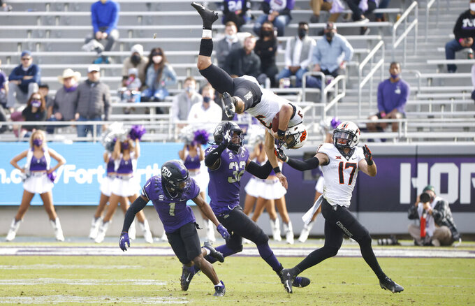 Oklahoma State quarterback Spencer Sanders (3) is hit and flipped in the air by TCU cornerback Tre'Vius Hodges-Tomlinson (1) as Oklahoma State wide receiver Dillon Stoner (17) TCU defensive end Ochaun Mathis (32) look on during the second half of an NCAA college football game Saturday, Dec. 5, 2020, in Fort Worth, Texas.  (AP Photo/Ron Jenkins)