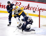 Winnipeg Jets' goaltender Connor Hellebuyck (37) makes a save as Nashville Predators' Yakov Trenin (32) looks for the rebound in front of Dmitry Kulikov (7) during first period NHL hockey action in Winnipeg, Manitoba, Sunday Jan. 12, 2020. (Fred Greenslade/The Canadian Press via AP)
