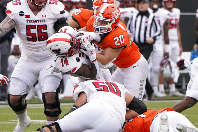 Texas Tech running back Xavier White (14) is tackled by Oklahoma State linebacker Malcolm Rodriguez (20) in the first half of an NCAA college football game in Stillwater, Okla., Saturday, Nov. 28, 2020. (AP Photo/Sue Ogrocki)