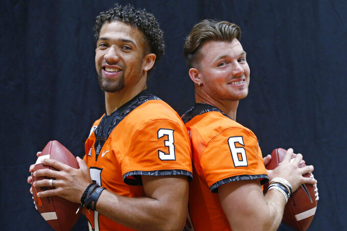 FILE - In this Saturday, Aug. 3, 2019, file photo, Oklahoma State quarterbacks Spencer Sanders, left, and Dru Brown, right, pose for a photo during the NCAA college football team's media day in Stillwater Okla. Oklahoma State coach Mike Gundy says he considers both capable of starting. (AP Photo/Sue Ogrocki, File)