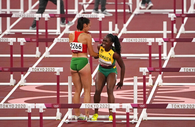 Luca Kozak, of Hungary, left, helps Yanique Thompson, of Jamaica, center, to her feet after both failed to finish a women's 100-meter hurdles semifinal at the 2020 Summer Olympics, Sunday, Aug. 1, 2021, in Tokyo, Japan. (AP Photo/Charlie Riedel)
