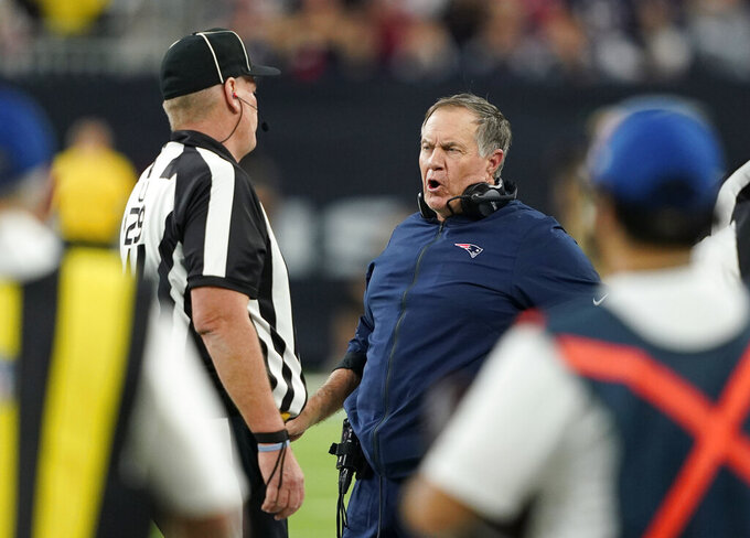 New England Patriots head coach Bill Belichick, center, questions a call during the first half of an NFL football game Sunday, Dec. 1, 2019, in Houston. (AP Photo/David J. Phillip)