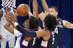 DePaul's Javon Freeman-Liberty (4) is triple-teamed by Connecticut's Brendan Adams (10) Isaiah Whaley (5) and Tyrese Martin during the second half of an NCAA college basketball game Monday, Jan. 11, 2021, in Chicago. (AP Photo/Charles Rex Arbogast)