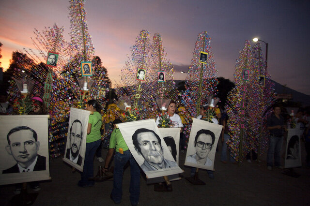 FILE - In this Nov. 15, 2008 file photo, people hold banners depicting six Jesuit priests massacred in 1989, during a memorial to mark the 19th anniversary of their death, in San Salvador. For years, attempts within El Salvador to investigate and prosecute the masterminds of the massacre during that country's civil war have been delayed and deflected by legal maneuvers. (Edgar Romero/AP Photo File)