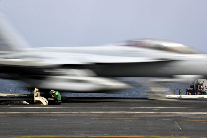 In this Thursday, May 16, 2019 photograph released by the U.S. Navy, Aviation Boatswain's Mate Airman Kayla Pettit operates a center deck station as an F-18 Super Hornet takes off from the USS Abraham Lincoln aircraft carrier in the Arabian Sea. On Saturday, May 18, 2019, U.S. diplomats warned that commercial airliners flying over the wider Persian Gulf faced a risk of being