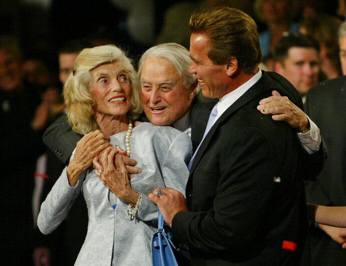 "FILE - This Oct. 7, 2003 file photo shows Republican Arnold Schwarzenegger, right, with his in-laws Eunice Kennedy-Shriver, left, and Sargent Shriver following his victory in the California gubernatorial recall election in Los Angeles. RosettaBooks announced Tuesday, July 7, 2020, that it had acquired Shriver's memoir ""We Called It a War,"" which he worked on in the late 1960s and was only recently rediscovered. Shriver's friend and law partner David Birenbaum edited the manuscript, in which Shriver tells of his efforts to fulfill Johnson's vow in 1964 to end poverty. The 348-page book, pared down from a ""very raw"" 500 pages, is scheduled for January. Shriver died Jan. 18, 2011 at age 95. (AP Photo/Chris Carlson, File)"
