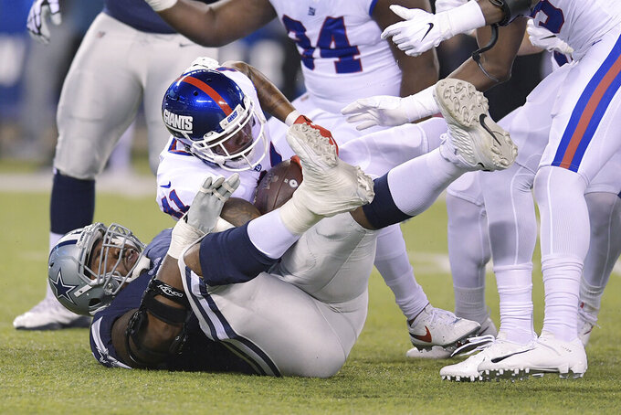 New York Giants free safety Antoine Bethea (41) is tackled by Dallas Cowboys offensive tackle Tyron Smith (77) after intercepting a pass during the first quarter of an NFL football game, Monday, Nov. 4, 2019, in East Rutherford, N.J. (AP Photo/Bill Kostroun)