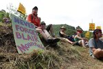 """Activists rest during a rally in Blair, W.Va., Saturday, June 11, 2011, where more than 1,000 people marched to the top of Blair Mountain to protest """"mountaintop removal"""" coal mining. The mountain, the site of a deadly battle involving unionizing coal miners and law enforcement officers in 1921, was restored to the National Register of Historic Places in 2018. (AP Photo/Brad Davis)"""