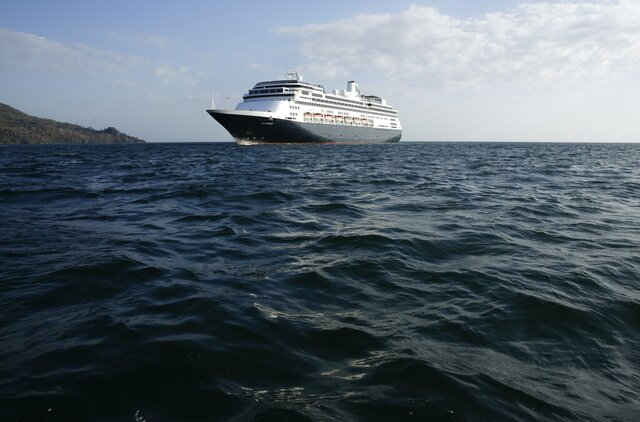 The Zaandam cruise ship is anchored in the bay of Panama City, Friday, March 27, 2020. Several passengers have died aboard the cruise ship and a few people aboard the ship have tested positive for the new coronavirus, the cruise line said Friday, with hundreds of passengers unsure how long they will remain at sea. (AP Photo/Arnulfo Franco)