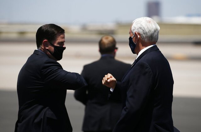 Vice President Mike Pence, right, is greeted with an elbow bump by Arizona Gov. Doug Ducey, left, as he arrives to discuss the surge in coronavirus cases Wednesday, July 1, 2020, in Phoenix. (AP Photo/Ross D. Franklin)