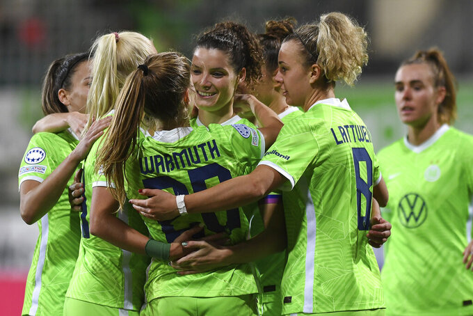 Wolfsburg's Dominique Janssen, center left, celebrates with teammates after scoring during the Women's Champions League group A soccer match between VfL Wolfsburg and Servette FC Chenois at AOK Stadion in Wolfsburg, Germany, Wednesday, Oct. 13, 2021. (Swen Pf'rtner/dpa via AP)