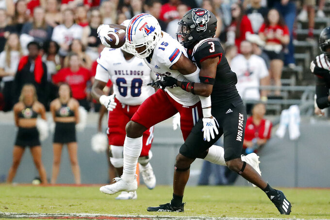 Louisiana Tech's Bub Means (15) tries to break away from North Carolina State's Aydan White (3) during the first half of an NCAA college football game in Raleigh, N.C., Saturday, Oct. 2, 2021. (AP Photo/Karl B DeBlaker)