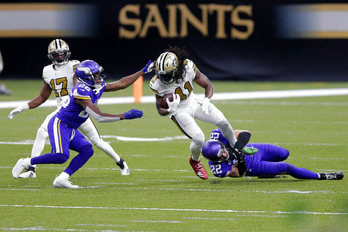 New Orleans Saints running back Alvin Kamara (41) is tackled by Minnesota Vikings strong safety Harrison Smith (22) and defensive back Chris Jones (26) in the first half of an NFL football game in New Orleans, Friday, Dec. 25, 2020. (AP Photo/Brett Duke)