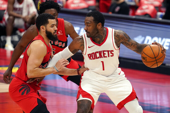 Houston Rockets guard John Wall (1) holds off Toronto Raptors guard Fred VanVleet (23) and forward Stanley Johnson (5) during the first half of an NBA basketball game Friday, Feb. 26, 2021, in Tampa, Fla. (AP Photo/Chris O'Meara)