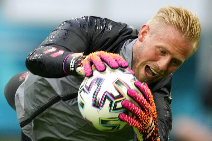 Denmark's goalkeeper Kasper Schmeichel dives for the ball during the training of his team at Johan Cruyff ArenA in Amsterdam, Netherlands, Friday, June 25, 2021, a day before the Euro 2020 soccer championship round of 16 match between Wales and Denmark. (AP Photo/Peter Dejong)