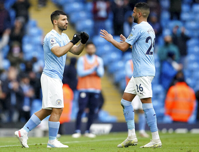 Manchester City's Sergio Aguero, left, is substituted for Manchester City's Riyad Mahrez during the English Premier League soccer match between Manchester City and Everton at the Etihad stadium in Manchester, Sunday, May 23, 2021.(AP Photo/Dave Thompson, Pool)