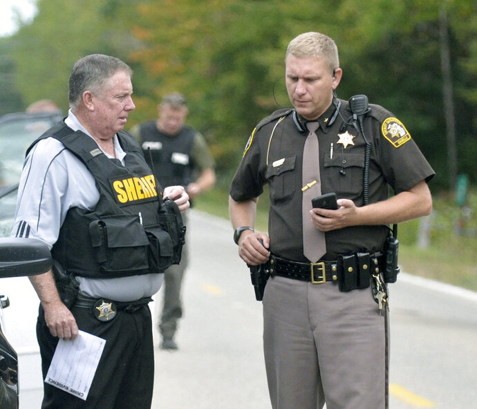 In this Sept. 27, 2017 photo, Isabella County Sheriff Michael Main, right, coordinates efforts in a police manhunt in rural Isabella County, Mich. Main is apologizing for accidentally leaving his gun in a mid-Michigan school gym locker room. Main said Tuesday, March 13, 2018 he takes full responsibility and is