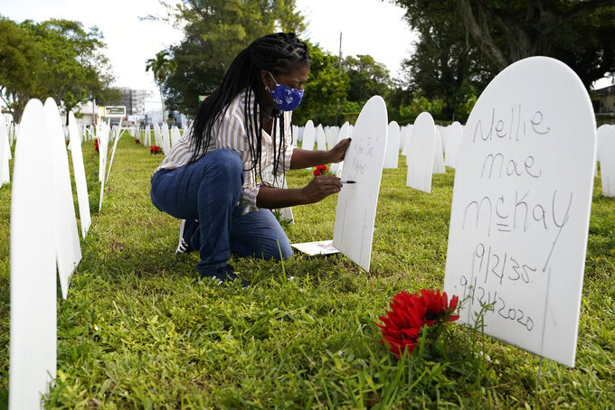 """FILE - In this Nov. 24, 2020, file photo, Joanna Moore writes a tribute to her cousin Wilton """"Bud"""" Mitchell who died of COVID-19 at a symbolic cemetery created to remember and honor lives lost to COVID-19, in the Liberty City neighborhood of Miami. The U.S. death toll from COVID-19 has topped 600,000, even as the vaccination drive has drastically slashed daily cases and deaths and allowed the country to emerge from the gloom. (AP Photo/Lynne Sladky, File)"""