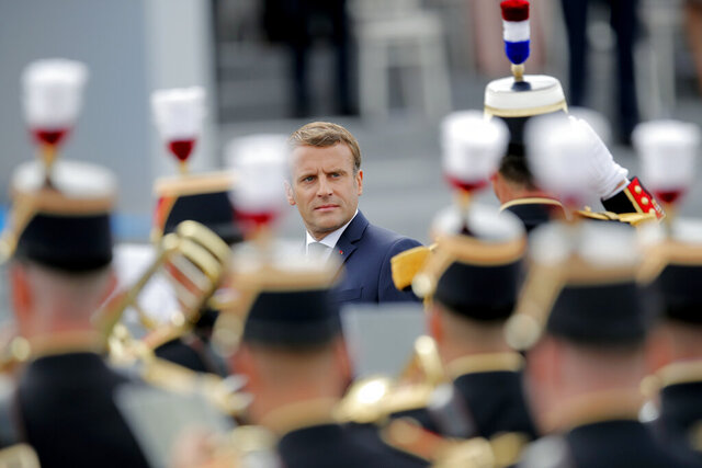 France's President Emmanuel Macron reviews troops before the start of the Bastille Day military parade, Tuesday, July 14, 2020 in Paris. France are honoring nurses, ambulance drivers, supermarket cashiers and others on its biggest national holiday Tuesday. Bastille Day's usual grandiose military parade in Paris is being redesigned this year to celebrate heroes of the coronavirus pandemic. (AP Photo/Christophe Ena, Pool)