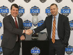 Virginia head coach Bronco Mendenhall, right, and South Carolina head coach Will Muschamp, left, pose for a photo during media day for the Belk Bowl NCAA college football game in Charlotte, N.C., Friday, Dec. 28, 2018. Virginia plays South Carolina on Saturday, Dec. 29, 2018. (AP Photo/Steve Reed)