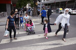 Turkish children under 14 with their parents wearing face masks for protection against the coronavirus, walk in popular Tunali Hilmi Street, in Ankara, Turkey, Wednesday, May 27, 2020. Children were allowed to go out between 12:00-15:00 local time for the third time. AP Photo/Burhan Ozbilici)