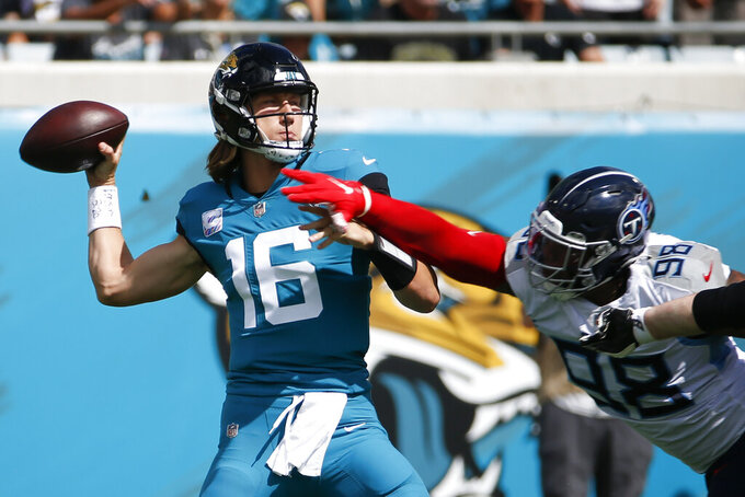 Jacksonville Jaguars quarterback Trevor Lawrence (16) throws a pass as he is pressured by Tennessee Titans defensive end Jeffery Simmons (98) during the first half of an NFL football game, Sunday, Oct. 10, 2021, in Jacksonville, Fla. (AP Photo/Stephen B. Morton)