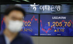 A currency trader wearing a face mask walks by the screens showing the foreign exchange rate between U.S. dollar and South Korean won at the foreign exchange dealing room in Seoul, South Korea, Friday, July 17, 2020. Asian stock markets rebounded Friday after Wall Street closed lower amid uncertainty about the U.S. economic outlook. (AP Photo/Lee Jin-man)