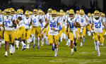 UCLA defensive back Grady Liddell (20) leads teammates onto the gridiron to face Colorado in an NCAA college football game Saturday, Nov. 7, 2020, in Boulder, Colo. (AP Photo/David Zalubowski)