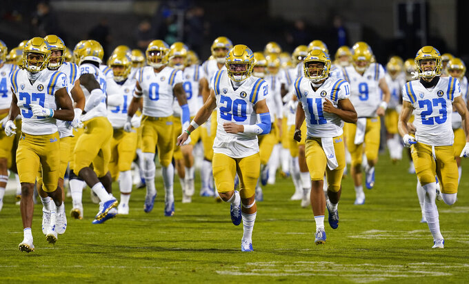 UCLA defensive back Grady Liddell (20) leads teammates onto the gridiron to face Colorado in an NCAA college football game Saturday, Nov. 7, 2020, in Boulder, Colo. (AP Photo/David Zalubowski)