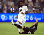 Sporting Kansas City midfielder Roger Espinoza (17) kicks the ball away from Minnesota United defender Romain Metanire (19) during the first half of an MLS soccer match in Kansas City, Kan., Thursday, Aug. 22, 2019. (AP Photo/Orlin Wagner)