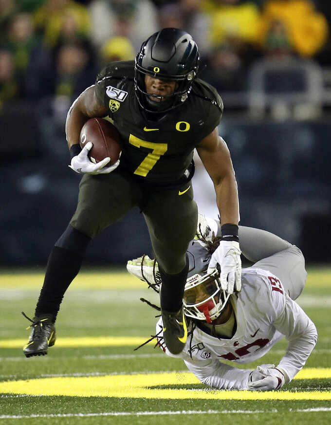 Oregon's CJ Verdell, left, breaks a tackle by Washington State's Jahad Woods during the third quarter of an NCAA college football game Saturday, Oct. 26, 2019, in Eugene, Ore. (AP Photo/Chris Pietsch)