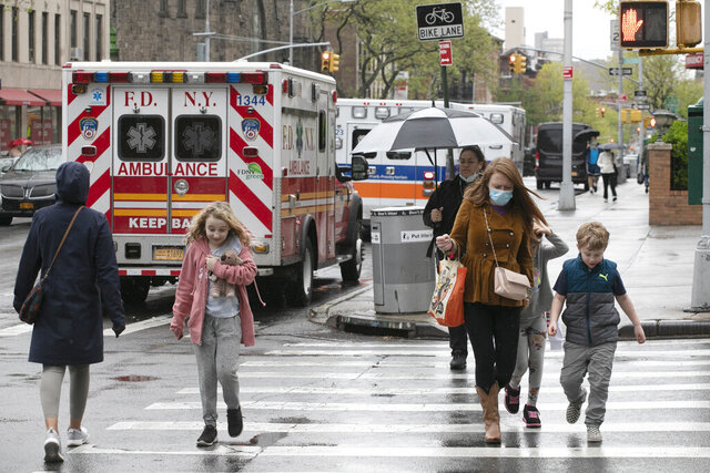People walk by ambulances parked outside NewYork–Presbyterian Brooklyn Methodist Hospital, Wednesday, May 6, 2020 in New York during the coronavirus pandemic. New York Gov. Andrew Cuomo says most COVID-19 patients coming into New York hospitals are not working and not traveling daily and tend to be older than 50. (AP Photo/Mark Lennihan)