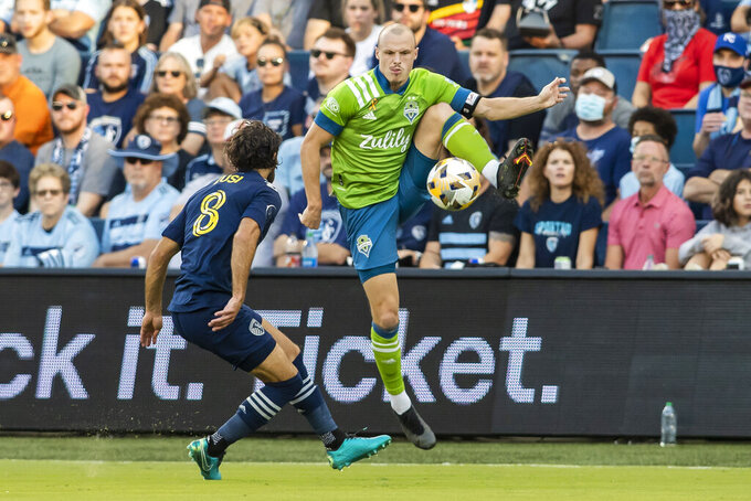 Seattle Sounders defender Brad Smith leaps up to bring down the ball during the first half of an MLS soccer match against the Seattle Sounders, Sunday, Sept. 26, 2021, in Kansas City, Kan. (AP Photo/Nick Tre. Smith)