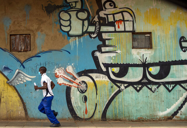 A man wearing face masks to protect against coronavirus, runs past a mural on the street in downtown Johannesburg, South Africa, Thursday, April 9, 2020. South Africa and more than half of Africa's 54 countries have imposed lockdowns, curfews, travel bans or other restrictions to try to contain the spread of COVID-19. The new coronavirus causes mild or moderate symptoms for most people, but for some, especially older adults and people with existing health problems, it can cause more severe illness or death. (AP Photo/Themba Hadebe)