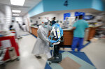 Medical equipment is rushed to a room as medical personnel try to save the life of a patient inside the Coronavirus Unit at United Memorial Medical Center, Monday, July 6, 2020, in Houston. Despite their efforts, the patient died. (AP Photo/David J. Phillip)