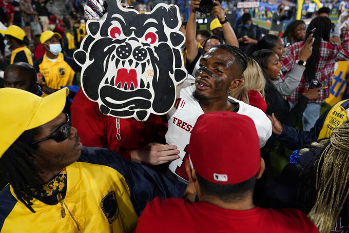 Fresno State wide receiver Keric Wheatfall holds a cutout of the school's mascot after a win over UCLA in an NCAA college football game Sunday, Sept. 19, 2021, in Pasadena, Calif. (AP Photo/Marcio Jose Sanchez)