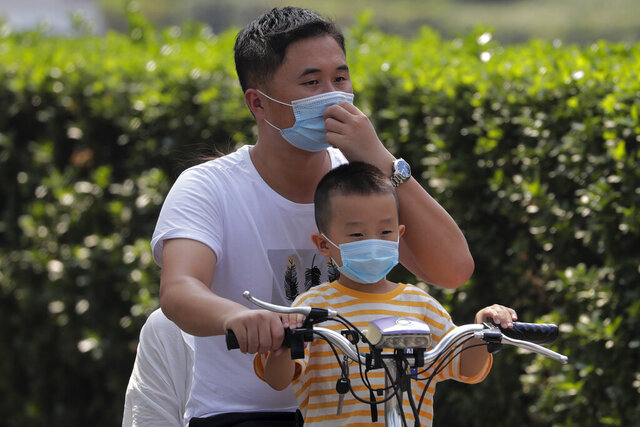 A man and a child wearing face masks to help curb the spread of the coronavirus ride on an electric-powered scooter past the Xinfadi wholesale food market district in Beijing, Sunday, Sept. 6, 2020. According to local news report, Xinfadi market, the capital's biggest wholesale food market have reopen for wholesale operation after it was shutdown following the coronavirus outbreak. China's government on Sunday reported several new coronavirus infections, all believed to have been acquired abroad, and no deaths. (AP Photo/Andy Wong)