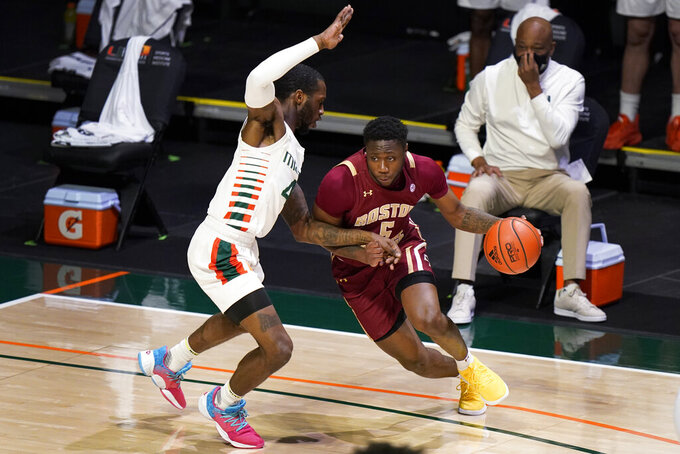 Boston College guard Jay Heath (5) drives up against Miami guard Elijah Olaniyi (4) during the first half of an NCAA college basketball game, Friday, March 5, 2021, in Coral Gables, Fla. (AP Photo/Wilfredo Lee)