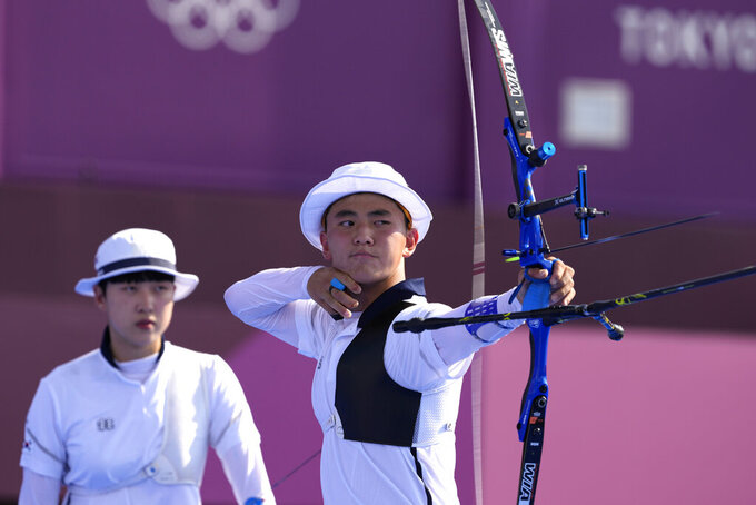 South Korea's Kim Je Deok releases an arrow flanked by his teammate An San during the mixed team competition at the 2020 Summer Olympics, Saturday, July 24, 2021, in Tokyo, Japan. (AP Photo/Alessandra Tarantino)