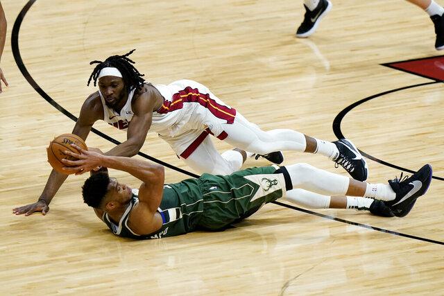 Milwaukee Bucks forward Giannis Antetokounmpo, bottom, and Miami Heat forward Precious Achiuwa go for a loose ball during the first half of an NBA basketball game Wednesday, Dec. 30, 2020, in Miami. (AP Photo/Lynne Sladky)
