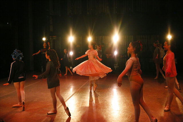 "Young dancers perform on stage during a rehearsal of Vladimir Issaev's rendition of The Nutcracker ballet on Friday, Dec. 13, 2019, in Fort Lauderdale, Fla. More than 20 dancers of Venezuelan origin were playing various roles on a recent performance of the holiday favorite ""The Nutcracker."" Some of these dancers are here seeking asylum after fleeing their crisis-torn nation, which is plagued by shortages of food and medicine.  (AP Photo/Brynn Anderson)"