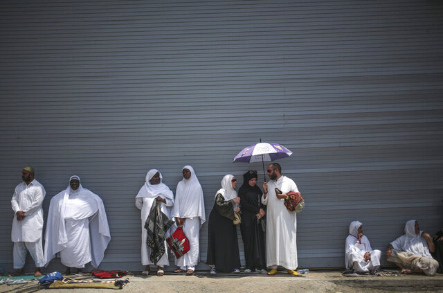 FILE - In this Sept. 18, 2015 file photo, Muslim pilgrims shelter themselves from the heat as they attend Friday afternoon prayers outside the Grand Mosque in the holy city of Mecca, Saudi Arabia. A new study released Monday, May 4, 2020, says 2 to 3.5 billion people in 50 years will be living in a climate that historically has proven just too hot to handle. Currently about 20 million people live in places with an annual average temperature greater than 84 degrees (29 degrees Celsius) — far beyond the temperature sweet spot. That area is less than 1% of the Earth's land, and it is mostly near the Sahara Desert and includes Mecca, Saudi Arabia.  (AP Photo/Mosa'ab Elshamy, File)