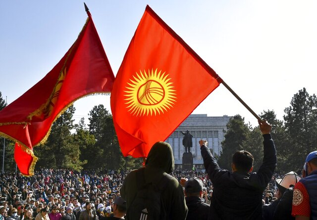 Protesters react waving Kyrgyz national flags as they wait for Kyrgyz Prime Minister Sadyr Zhaparov speech in front of the government building in Bishkek, Kyrgyzstan, Wednesday, Oct. 14, 2020. Kyrgyzstan's embattled president has discussed his possible resignation with his newly appointed prime minister in a bid to end the political crisis in the Central Asian country after a disputed parliamentary election. President Sooronbai Jeenbekov held talks with Prime Minister Sadyr Zhaparov a day after refusing to appoint him to the post over concerns whether parliament could legitimately nominate him. (AP Photo/Vladimir Voronin)