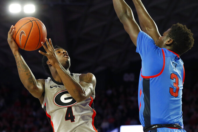 Georgia's Tyree Crump (4) shoots while being defended by Mississippi forward Khadim Sy (3) during an NCAA college basketball game in Athens, Ga., Saturday, Jan. 25, 2020. (Joshua L. Jones/Athens Banner-Herald via AP)