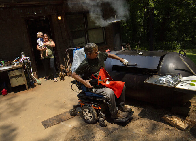 Jennifer Howard retrieves grandson Xander from husband Bobby Howard's workshop at their Morganfield, Ky., home Wednesday afternoon, July 14, 2021, as Bobby was about to pull a couple rolls of smoked bologna from the custom smoker he created. Nearly 17 years after a car accident that left Bobby Howard paralyzed from the waist down, the Morganfield man still clings to an attitude that kept him going after it first happened. Whether he's building a new barbecue smoker, modifying a vehicle to suit his needs or keeping up with his four grandchildren, any obstacle posed by his wheelchair or various health issues is just a new challenge to overcome. (Denny Simmons/Evansville Courier & Press via AP)