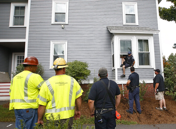 As a Columbia Gas employees looks on, left, an Andover, Mass. police officer comes out the window of an evacuated house after checking that there is no presence of gas and that the gas in the house is turned off Friday, Sept. 14, 2018, in Andover, Mass. Multiple houses were damaged Thursday afternoon from gas explosions and fires triggered by a problem with a gas line that feeds homes in several communities north of Boston.(AP Photo/Winslow Townson)