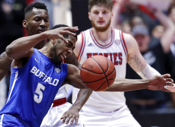 Buffalo guard C.J. Massinburg (5) controls the ball against Northern Illinois guard Eugene German during the second half of an NCAA college basketball game Tuesday, Jan. 22, 2019, in DeKalb, Ill. Northern Illinois won 77-75. (AP Photo/Nam Y. Huh)