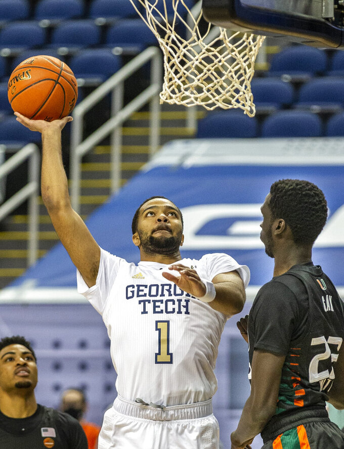 Georgia Tech's Kyle Sturdivant (1) puts up a shot as Miami's Kameron McGusty, right, defends during an NCAA college basketball game in the quarterfinal round of the Atlantic Coast Conference tournament in Greensboro, N.C., Thursday, March 11, 2021. (Woody Marshall/News & Record via AP)