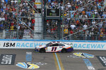 Denny Hamlin (11) takes the checkered flag to win the NASCAR Cup Series auto race Sunday, Nov. 10, 2019, in Avondale, Ariz. (AP Photo/Ralph Freso)